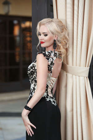 Beautiful blond lady in elegant dress. Hairstyle. Red lips makeup. Attractive fashion girl model in black evening gown. outdoor photo Stock Photo
