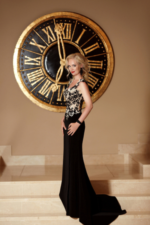 Elegant lady in fashion long black dress posing in front of wall clock, time. Glamour. Luxury life. Beauty fashion indoor portrait photo.
