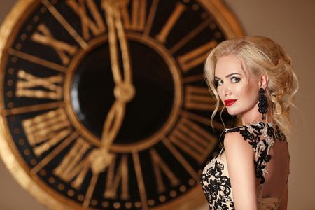 エレガントな女性メイク ang 金髪髪型、黄金色の壁時計の前でポーズします。美容ファッション屋内ポートレート写真。