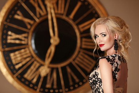 Elegant lady with makeup ang blond hairstyle posing in front of wall clock, golden colors. Beauty fashion indoor portrait photo.