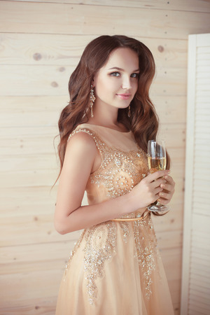 Party, drinks. Beautiful elegant woman in evening dress with champagne glass over beige wooden background. party celebration Stock Photo