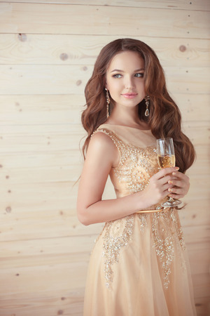 Party, drinks. Beautiful elegant woman in evening dress with glass of sparkling wine over beige wooden background. party celebration