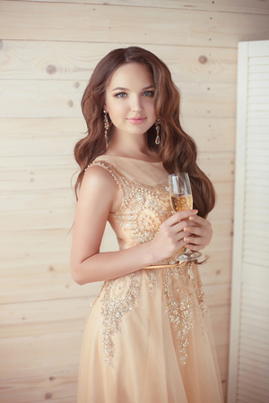 Party celebration, drinks. Beautiful elegant woman in evening dress with champagne glass over beige wooden background. party celebration