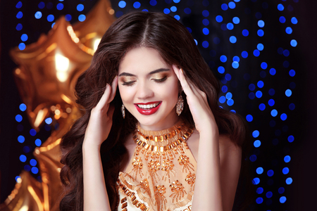 gorgeous, happy smiling young woman with red lips, in luxury golden dress laughing over blue party light background. Happiness.