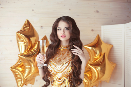 Beautiful fashion woman holding wine glass propose a toast.  party, drinks, holidays, celebrate and people concept. Brunette in golden dress over gold star balloons
