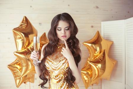 donne eleganti: celebrazione del partito, splendida giovane donna nel pensiero abito dorato e tenendo il bicchiere del processo brindisi di champagne su palloni d'oro stella di fronte a sfondo beige di legno.
