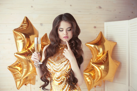 party celebration, gorgeous young woman in golden dress thinking and holding glass of champagne making toast over gold star balloons in front of wooden beige background.
