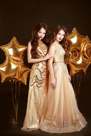 Elegant ladies on party. Beautiful sexy girls wearing in gold fashion dress posing with stars balloons isolated on black background. Celebrating.