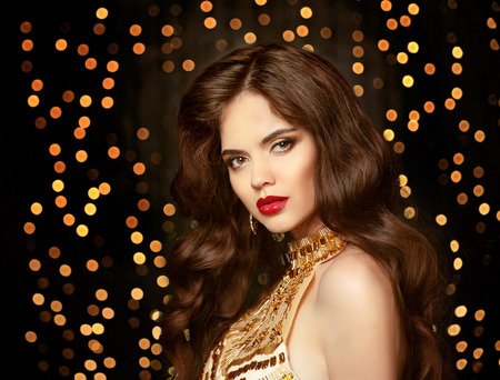 Beautiful Brunette girl with long shiny wavy hair. Elegant lady in gold. Fashion model with curly hairstyle. Red lips makeup. Glamour girl posing on Christmas party lights background.