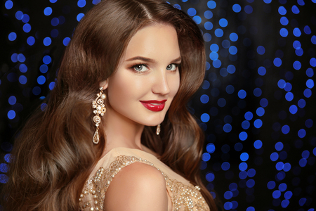 Beautiful elegant model brunette with long wavy hair and jewelry earrings isolated on holiday blue party lights background. Stock Photo