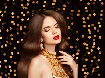 Beauty Makeup. Beautiful brunette girl with long wavy hairstyle. Healthy hair. Red lips. Elegant lady with expensive jewelry posing in golden dress over Christmas party light background.