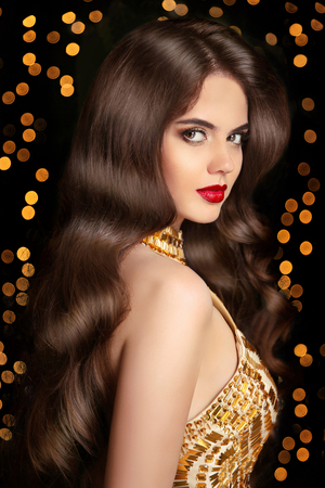 Long hair. Brunette girl with shiny wavy hairstyle and red lips makeup. Elegant lady posing in golden dress over Christmas party light background. glamour fashion model portrait.