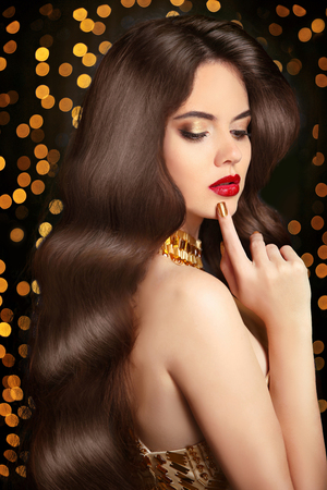 Long Healthy hair. Beauty portrait woman. red lips makeup. elegant lady with smooth shiny luxurious hairstyle posing in golden dress over Christmas party light background. Stock Photo