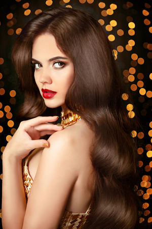 Long Healthy hair. beauty portrait woman. red lips makeup. elegant lady with smooth shiny luxurious hairstyle posing in golden dress over Christmas party light background.