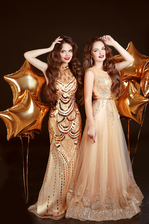 Two women in fashion dress, party celebration. Brunette twins girls posing with star balloons in golden elegant gown isolated on dark studio background. Фото со стока