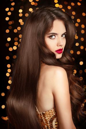 elegant party: Healthy hair. Makeup. Beautiful brunette girl with long wavy hairstyle. Red lips. Elegant lady with expensive jewelry posing in golden dress over Christmas party light background.