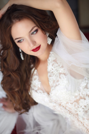 Beautiful smiling bride woman. Wedding Makeup. Attractive young girl model with long wavy hair wearing in white sexy boudoir dressing gown, beauty portrait.