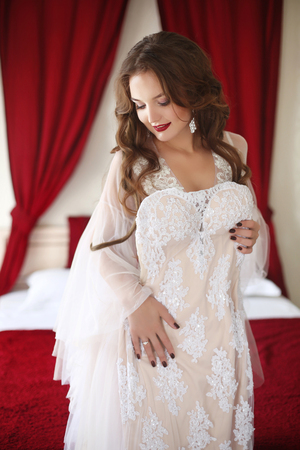 Beautiful smiling bride woman trying on wedding dress. Attractive young girl model with long wavy hair wearing in white sexy boudoir dressing gown, beauty portrait. Stock Photo