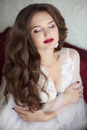 Beautiful brunette bride woman. Wedding Makeup. Attractive young girl model with long wavy hair wearing in white sexy boudoir dressing gown, beauty portrait.