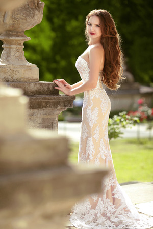 Bride. Wedding outdoor portrait of gorgeous brunette model with long wavy hair wearing in white fashion dress posing by classic flower pot at green park.