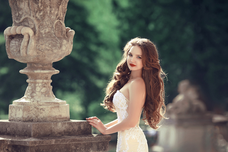 Bride. Wedding outdoor portrait of gorgeous brunette woman with long wavy hair wearing in white fashion dress posing by classic flower pot at green park. Stock Photo