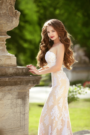 Wedding Portrait Of gorgeous Bride with long wavy hair wearing in white lace wedding dress holding posing in green park. Stock Photo