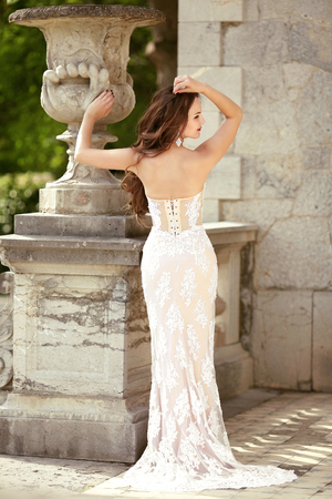 Beautiful bride in fashion wedding dress posng by roman flower pot, outdoors photo.