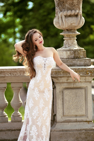 Beautiful bride wedding portrait, vogue style photo. Fashion brunette model posing in prom white dress by roman flower pot at green park, outdoor portrait.