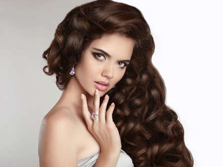 perming: Brunette girl with long shiny wavy hair. Beauty makeup. Beautiful model with curly hairstyle isolated on studio background. Fashion jewelry. Head and shoulders.