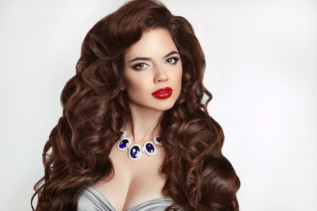 red lips: Curly hairstyle. Makeup. Beautiful brunette girl model with sensual red lips and long hair style, expensive gems jewelry  isolated on studio background. Elegant lady.