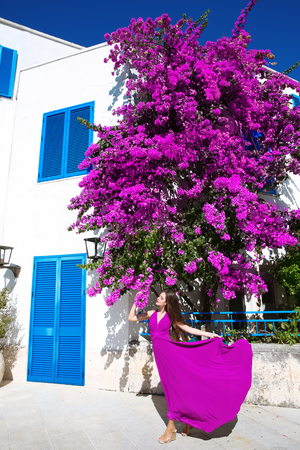 bougainvillea: Beautiful young Woman in blowing dress before purple bougainvillea tree and famous white village with blue windows. Summer vacation. Europe Greece Santorini travel vacation. Stock Photo