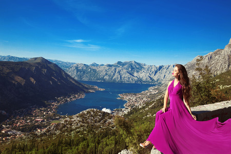background person: Kotor bay. Montenegro. Romantic Woman in blowing dress above Landscape of mountain ridge and Boka Kotorska. Adriatic sea.