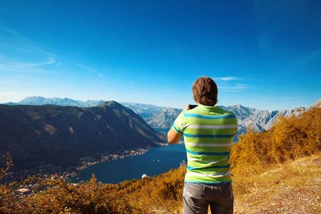 balkans: Kotor. Montenegro. Back view of young man tourist taking photo of mountain ridge and Boka Kotorska. Travel. Balkans. Trip. Vacation. Stock Photo