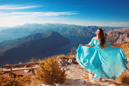 cruise travel: Montenegro landscape above Kotor bay. Beautiful woman in blowing dress posing on the top of mountain enjoy the beauty famous travel destination of seascape. Young girl love wild life, travel, freedom.