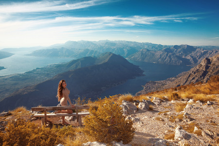 SEA  LANDSCAPE: Kotor bay. Montenegro. Romantic Woman on bench above Landscape of mountain ridge and Boka Kotorska. Adriatic sea. Aerial View Stock Photo