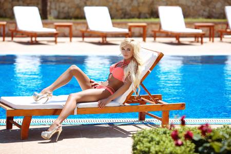 Modelo atractivo hermoso bikini mujer bronceada y acostado en silla de cubierta por la piscina azul, vacaciones de verano. Recurso. el cuidado del cuerpo sano.