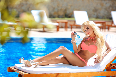 Beautiful woman bikini model tanned and lying on deck chair by the blue swimming pool,summer vacation. Resort. Healthy body care. Stock Photo