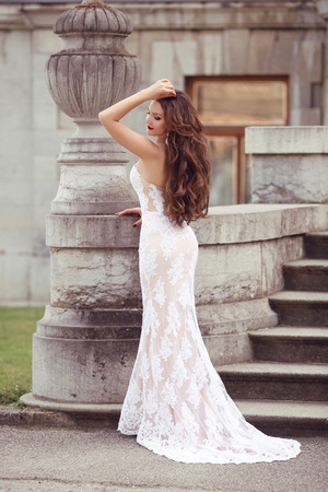 adult mermaid: Elegant bride woman wedding portrait, vogue style photo. Fashion brunette model posing in white mermaid dress by vase sculpture. Long Wavy hair.