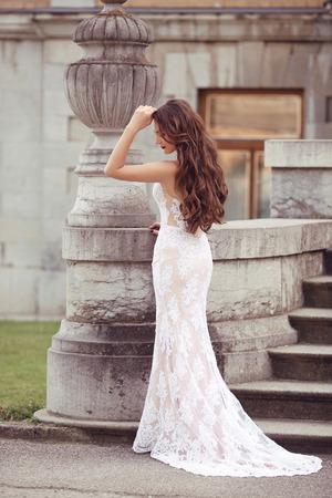 Elégant portrait de mariage mariée femme, photo de style vogue. brunette modèle de mode posant en robe sirène blanche par la sculpture de vase. De longs cheveux ondulés.