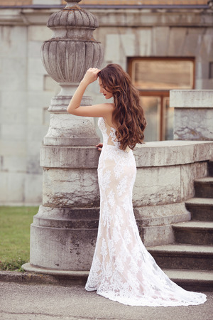 Elegant bride woman wedding portrait, vogue style photo. Fashion brunette model posing in white mermaid dress by vase sculpture. Long Wavy hair.