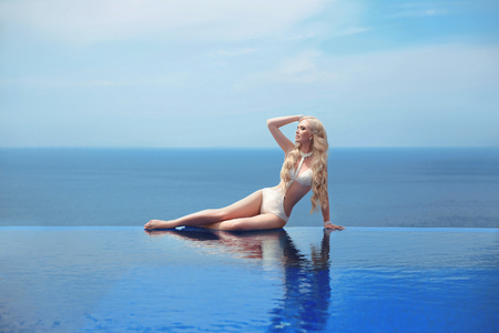 Beautiful sexy woman in white swimsuit, blond model tanned and lying on border of infinity swimming pool over blue sky, summer vacation. Resort. Healthy body care.