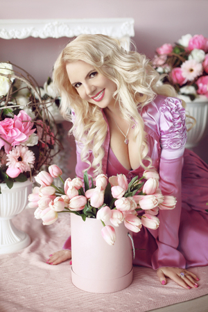 beautiful flowers: Beautiful happy smiling blond woman with long wavy hair style in the purple dress holding bouquet of tulips flowers in pink Hat Box over party gifts background