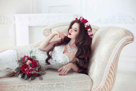 Beautiful brunette Bride wedding Portrait. Red lips makeup. Long wavy hair style. Expensive diamond jewelry. Bridal bouquet of flowers. Elegant lady lying on modern sofa in white interior. Stock Photo