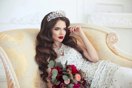 Beautiful brunette Bride wedding Portrait. Red lips makeup. Long wavy hair style. Expensive diamond jewelry. Bridal bouquet of flowers. Elegant lady lying on modern sofa in white interior. Archivio Fotografico