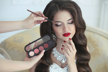 Beautiful brunette bride wedding portrait with makeup and hairstyle. Red lips and manicure nails. Stylist makes make-up model on wedding day. portrait of young woman at morning.