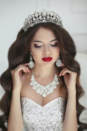 Beautiful bride makeup, fashion jewelry. Elegant brunette woman with long wavy hair style and red lips makeup in wedding dress posing in white interior. Фото со стока