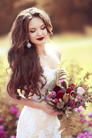 ramo de flores: Retrato de boda de la novia hermosa morena con el pelo largo y ondulado ramo de flores color de rosa posando en el parque del otoño que sostiene.