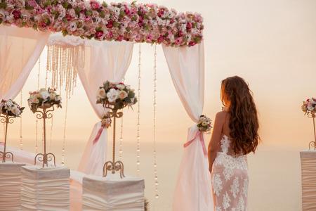 Huwelijksceremonie. Brunette bruid staande door krans boog met bloemstuk en wit gordijn op de klif boven zee, outdoor zomer foto. Bridal dag. Zonsondergang. Stockfoto