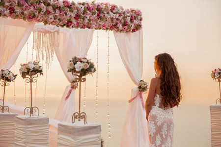 Wedding ceremony. Brunette bride standing by wreath arch with flower arrangement and white curtain on cliff above sea, outdoor summer photo. Bridal day. Sunset. Фото со стока