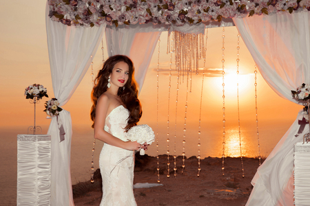 cliffs: Brunette bride portrait. Wedding ceremony arch with flower arrangement and white curtain on cliff above sea at sunset, outdoor photo.